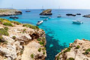 Beautiful blue lagoon with turquoise clear water, yachts and boats on a sunny summer day. Comino, Malta
