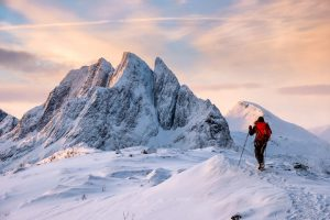 Mountaineer man climbs on top snowy mountain with colorful sky in morning